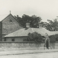 Image: a brick convent building behind a stone wall.
