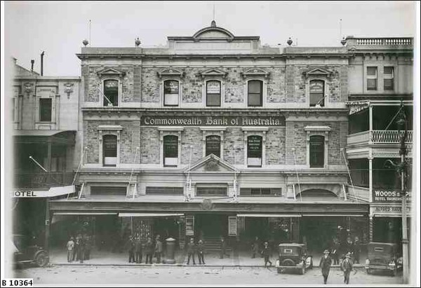 Image: a three storey stone terrace building with a verandah and triangular pediments over the rectangular windows.