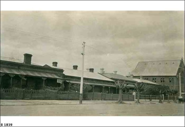 Image: a street-scape featuring a row of single storey cottages with tin roofs and verandahs behind picket fences. At the far right of the image a small stone church can be seen. The street is also lined with heavily pruned trees and telegraph poles.