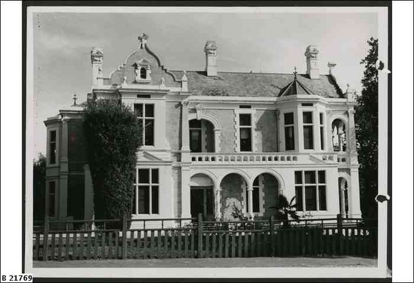 Image: A two storey house with a pitched roof, decorative gable, bay windows and a arched verandah/balcony