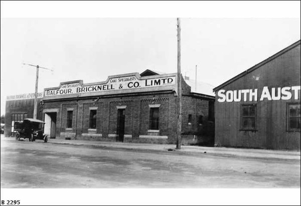 """Image: a single storey brick building with a low pitched roof behind a parapet sign reading """"Balfour, Bricknell & Co. Ltd. Cake Specialists"""". To the right is a corrugated iron building with part of a sign visible reading """"South Aust"""""""