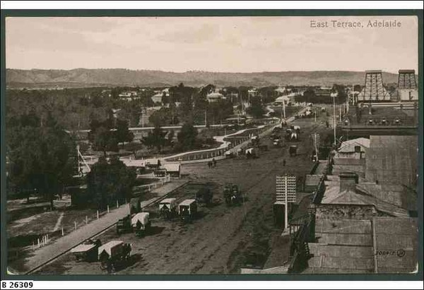 Image: A wide city street is lined with large buildings and a power station on one side and parklands on the other. A number of horse drawn vehicles are using the street.