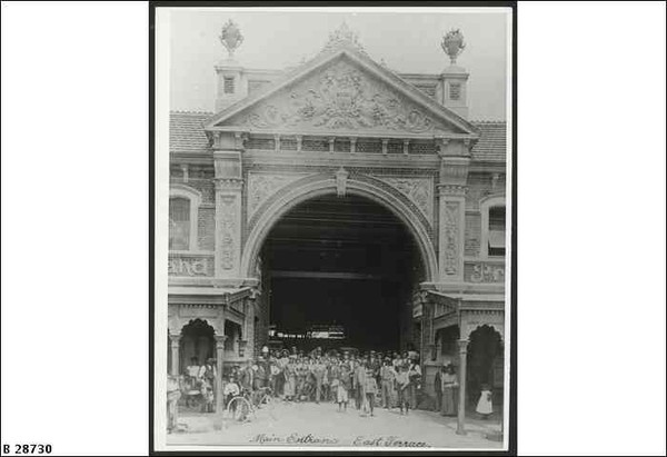 Image: A large group of people men, women and children pose under a huge two-storey high archway with a decorative pediment set within a brick terrace building fronted on either side of the arch with verandahs.