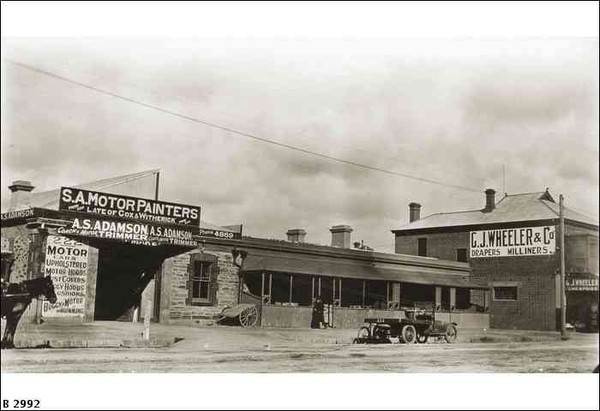 Image: a street-scape with a single storey stone workshop on the left, a hand barrow in front of it, a terraced row of cottages with verandahs in the centre of the image, a 1920s truck parked in front, and a two storey building to the right.