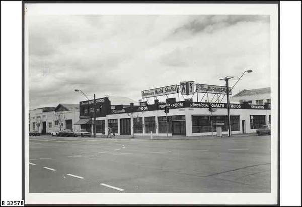 Image: a single storey concrete building with a flat roof on the corner of two main roads. The building is being used as a health studio with signs advertising a pool inside. 1970s era cars are parked outside.
