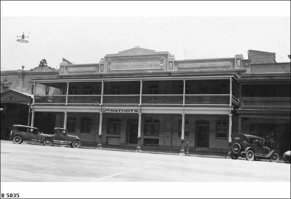 Image: A two storey hotel with balcony set within a terrace. 1920s era cars are parked on the street outside.