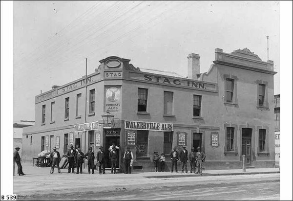 Image: A group of men stand outside a two storey corner hotel. Signs name it the Stag Inn and advertise Walkerville Ales for sale.
