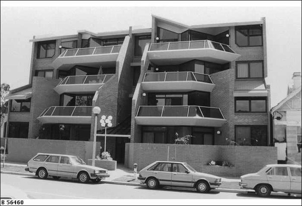 "Image: Three 1980s era cars are parked in front of four-storey 1980s ""modern"" brick townhouses with angular glass railed balconies."