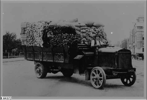 Image: A man sits in the driver's seat of a early 20th century truck heavily loaded with fruits and vegetables.