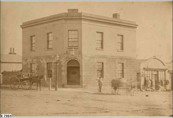 Image: a two storey corner hotel with an exposed stone façade on its lower floor and a rendered upper floor. A lantern hangs over the arched door on the corner, a double-hung window above with two more windows per floor on each side of the building.