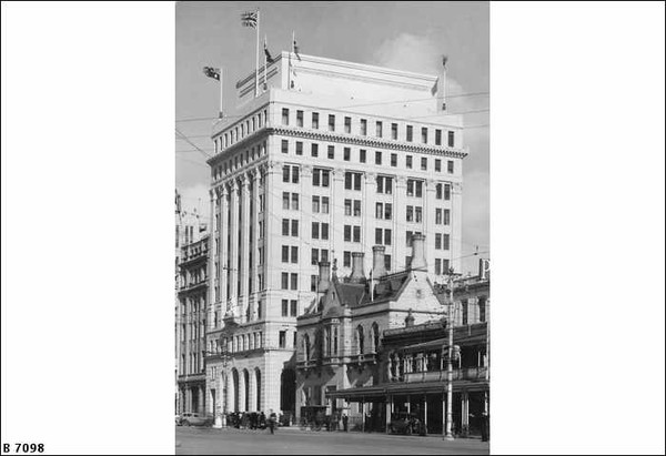 Image: a large building of at least ten storeys with a square floor plan, flags flying from poles on the roof, and arches on the ground floor.