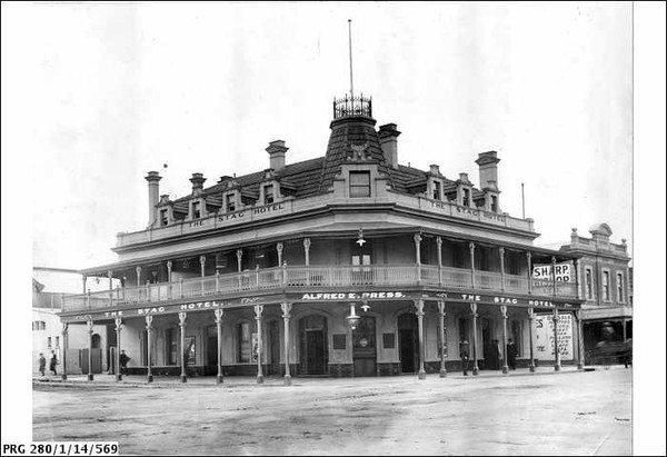 Image: A large corner building with balcony, mansard roof, and flagpole