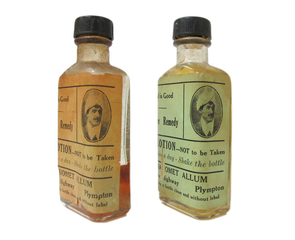 Image: two rectangular glass bottles with orange and green labels