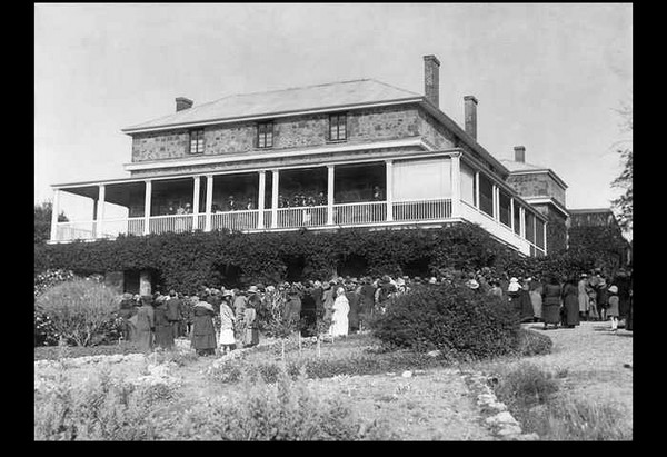 Image: A large, three-storey stone stately home with wraparound second-storey verandah. A group of people are gathered outside at the front of the house
