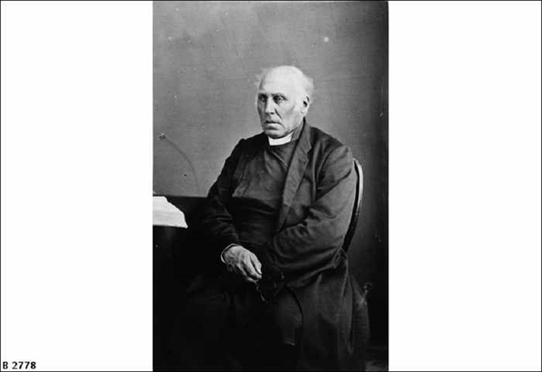 Image: Black and white photograph of seated elderly man wearing a clerical collar