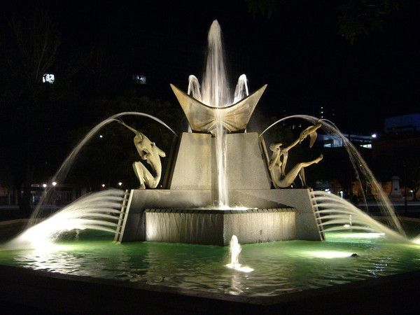Image: large fountain featuring human figures and birds lit up at night