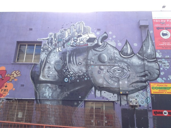 Image: blue and purple mural of a rhinoceros on a brick wall
