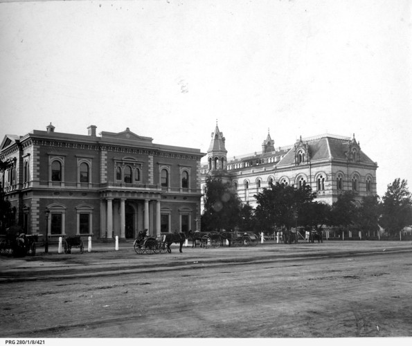 Image: view from street of two large ornate buildings with horse-drawn carts in the front
