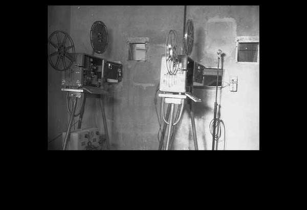 Image: Two film projectors of 1940s vintage stand in a projection room that is likely located within a cinema