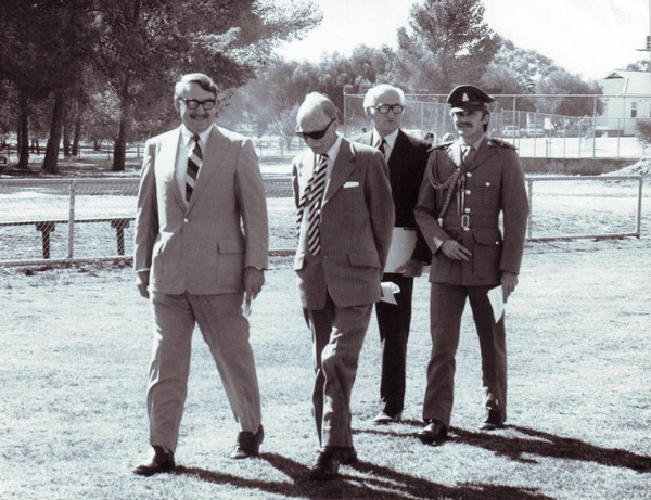 Image: Four men walk together as a group along the periphery of a parkland. Three are dressed in suits while the fourth wears a military-style uniform