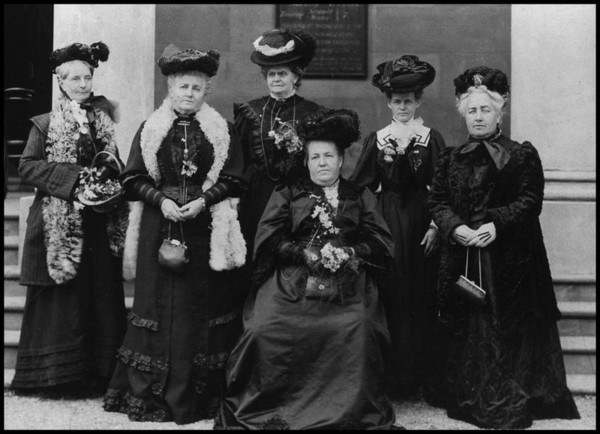 Image: photo of six women wearing black hats and dresses