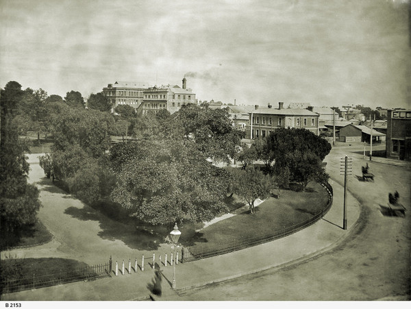 Image: View of city garden square with carts driving around
