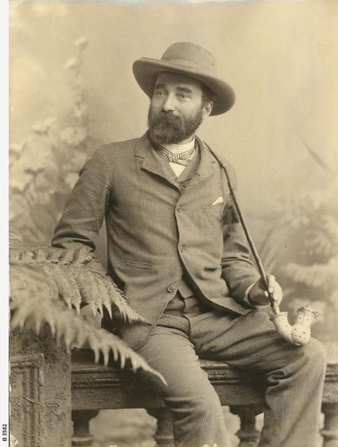 Image: sepia image of seated man wearing hat