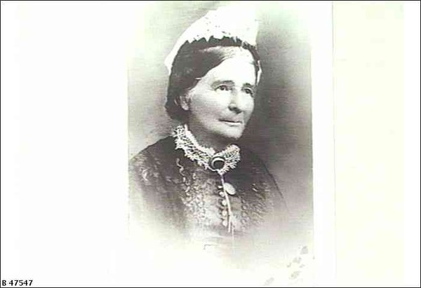 Image: A photographic head-and-shoulders portrait of a middle-aged woman in Victorian attire
