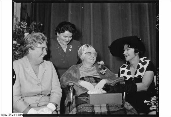 Image: A middle-aged Caucasian woman sits in a wheelchair and is wearing a fur stole and horn-rimmed glasses. Around her are seated three younger Caucasian women in formal dress