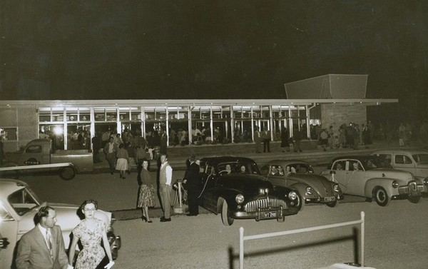 Image: parked cars and people milling around