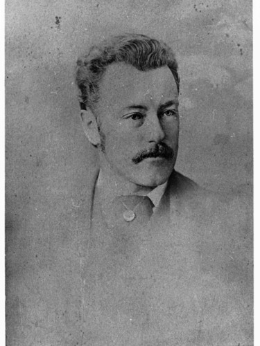 Image: A photographic head-and-shoulders portrait of a young, moustachioed man dressed in Victorian attire. He is wearing a cravat with a large pin or pendant embedded within it