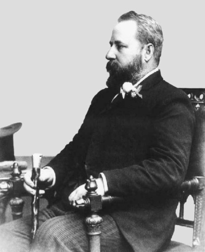 Image: black and white photograph of a seated man, dressed in black and holding a cane