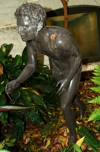 Image: bronze statue of young naked boy in running pose