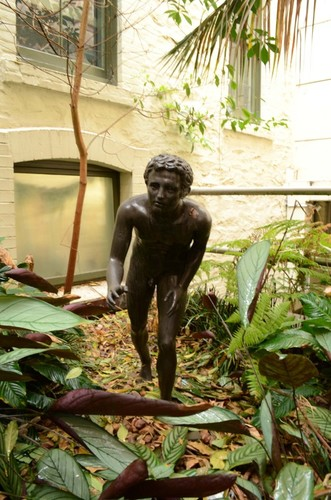 Image: bronze statue of a young naked boy in running pose