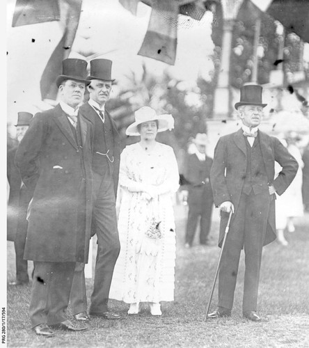 Image: woman in white dress and hat standing among three men in tophats and tails