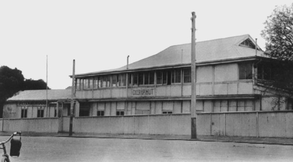 Image: Black and white photograph of a two storey building with a sign reading 'Cheer Up Hut' painted on the sign. A bag draped over the handlebars of a bicycle is just visible in the bottom left corner of the photograph.