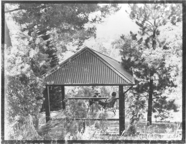 Image: Two men sit under a gazebo-like structure surrounded by trees