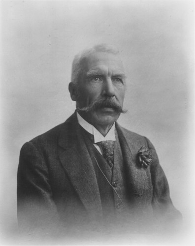 Image: Portrait photograph of a man wearing a suit and tie. He has a large mustache and his hair is white