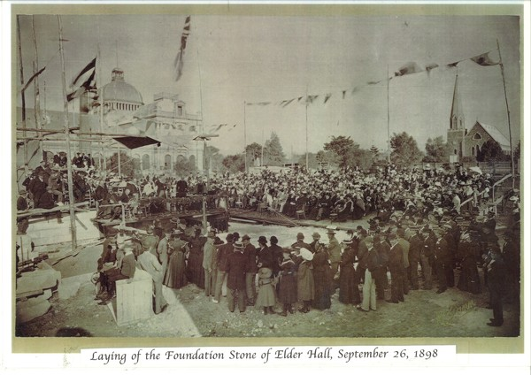 Image: A large group of people gather around a stage watching the foundation stone of Elder Hall being laid.