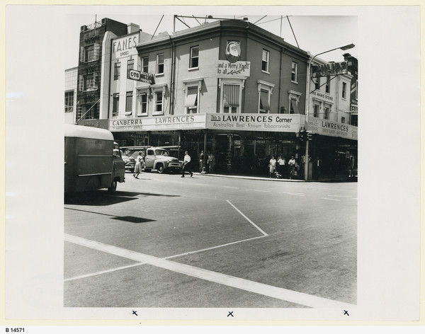 Image: a three storey corner shop with verandah. 1960s cars pass in front.