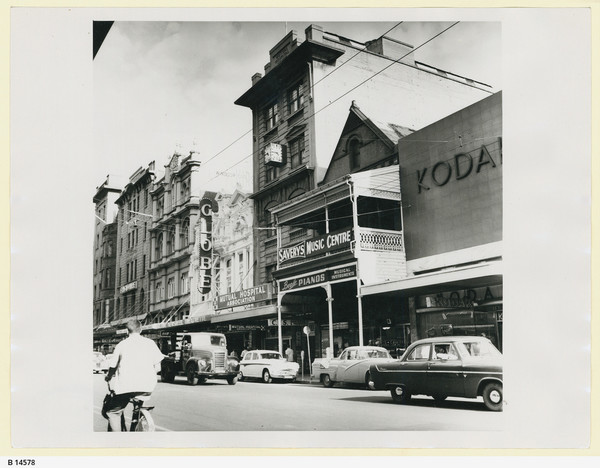 Image: 1960s cars (and a man on a bicycle) pass in front of a row of much older buildings. One of these, the Globe Theatre, is particularly ornate.