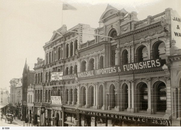 Image: a grand four storey department store with a highly decorative facade. The ground floor has plate glass windows with displays with the remainder of the floors having a large number of arched windows.