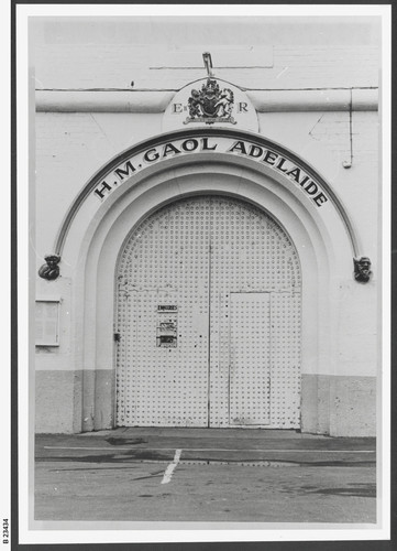 """Image: a large metal arched door with a sign reading: """"H.M. Gaol Adelaide"""""""