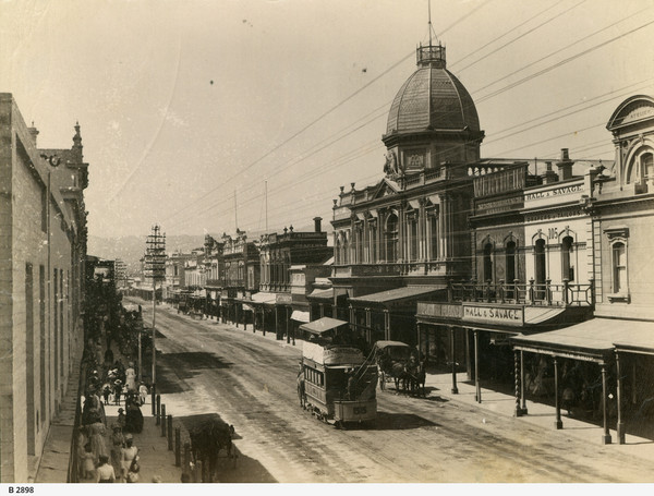 Image: a city street with a number of pedestrians and a horse drawn bus. Towards the centre of the view is an ornate two storey building with a dome.