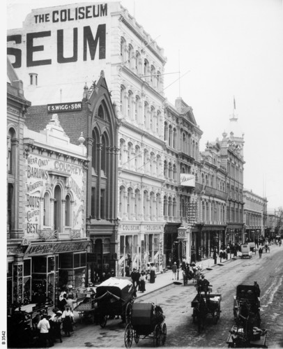 Image: a busy city street lined with three to five storey buildings. There is a single motor car amongst the horse drawn vehicles travelling down the dirt road which also hosts a number of street vendors and their carts.