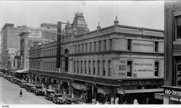 "Image: A three storey department store on a busy city street. A large number of 1930s era cars are parked outside and the sidewalk is busy with people, particularly women. Signs on the building identify it as ""The Big Store"""