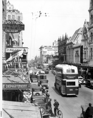 Image: 1920s and 1930s era cars, men on bicycles and a double decker bus travel down a busy city street lined with a large number of shops and a theatre
