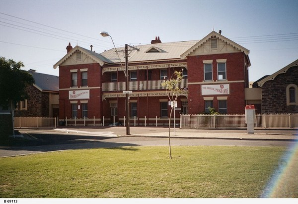 Image: A two-storey brick building with signs advertising the Salvation Army stands near the edge of a park