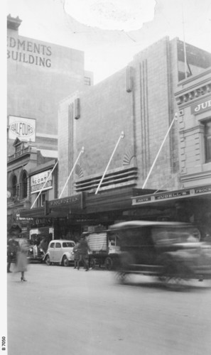 Image: 1930s era cars speed past the art deco facade of the new Woolworths building