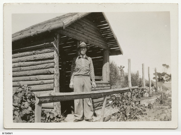 Image: man stands next to building made of logs